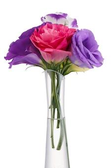 Buquê de flores coloridas eustoma em um vaso de vidro isolado na superfície branca