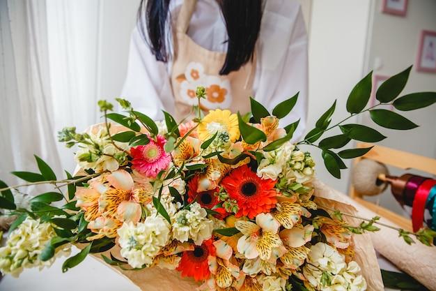 Buquê de flores coloridas frescas embrulhado em papel na mesa do florista.