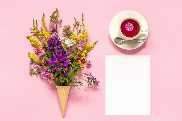 Buquê de flores coloridas no sorvete waffle cone, xícara de chá e cartão de papel em branco