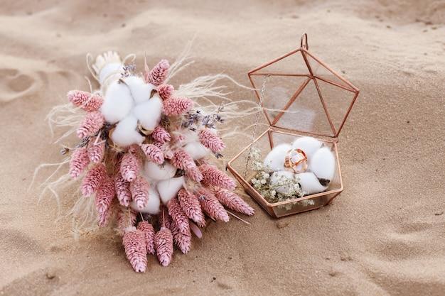 Buquê de flores com alianças em um caixão de vidro