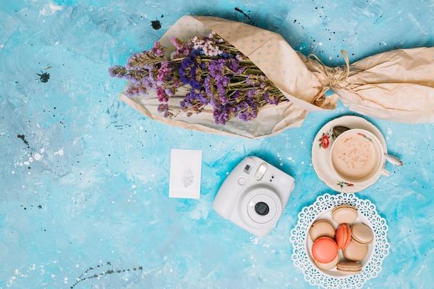 Buquê de flores com câmera instantânea, xícara de café e biscoitos