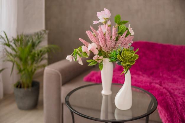 Buquê de flores com lindas flores alaranjadas, roxas, cacto artificial e suculento na mesa de vidro, palmeira e sofá