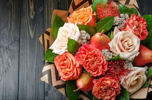 Buquê de flores com peras sobre um fundo escuro de madeira. buquê de frutas.
