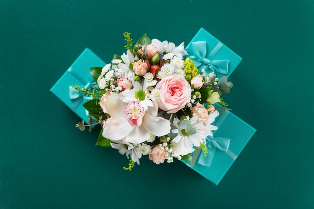 Buquê de flores com presente sobre fundo verde plano leigos, vista superior. são valentim, conceito de amor