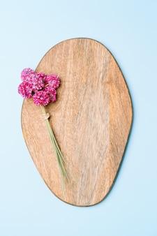 Buquê de flores cor de rosa na placa de madeira em fundo rosa, copie o espaço.