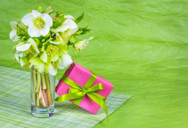 Buquê de flores da primavera e caixa com presente na mesa verde