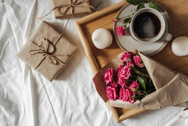 Buquê de flores da primavera e uma xícara de café em uma bandeja de madeira na cama