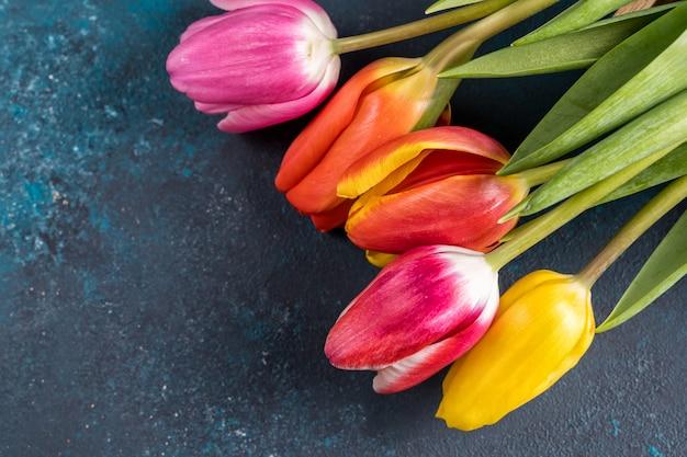 Buquê de flores da primavera. lindas tulipas em fundo azul brilhante de cor rústica. vista superior, copie o espaço.
