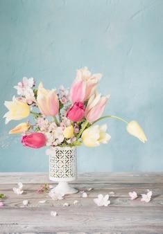Buquê de flores da primavera no fundo da velha parede azul