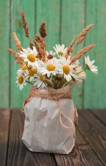 Buquê de flores de camomila branca com orelhas secas em um vaso de papel kraft