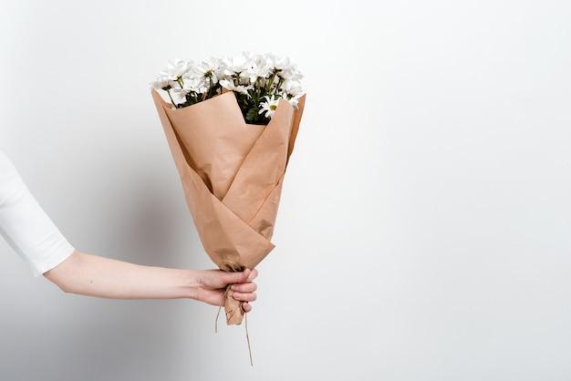 Buquê de flores de camomila na mão feminina contra uma parede branca