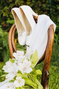 Buquê de flores de casamento; saltos altos e lenço na cadeira de madeira no parque