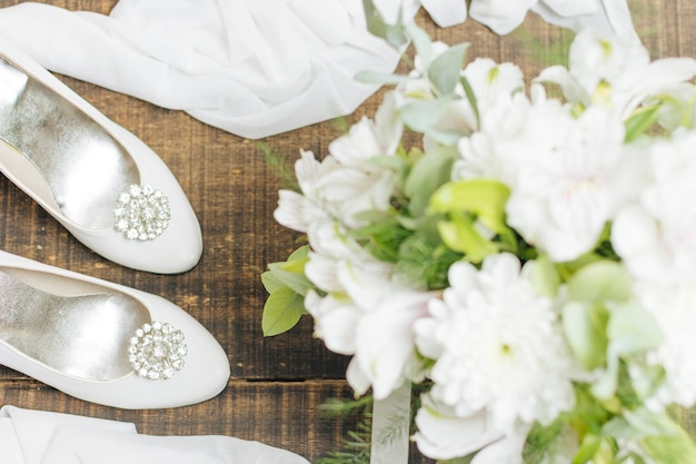 Buquê de flores de casamento; saltos altos e lenço na cadeira de madeira