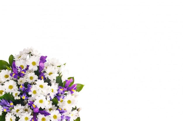 Buquê de flores de chamomiles e íris em uma parede branca