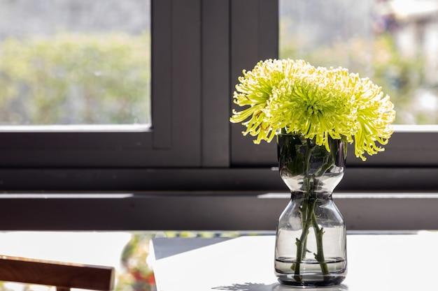 Buquê de flores de crisântemo verde lindo turva em vaso de vidro em cima da mesa.