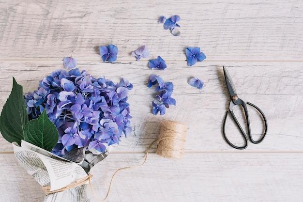 Buquê de flores de hortênsia roxa amarrado com carretel e tesoura na mesa de madeira