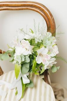 Buquê de flores de jasminum auriculatum de casamento na cadeira de madeira