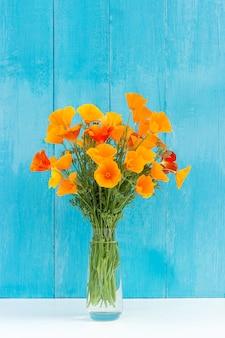 Buquê de flores de laranja brilhantes em um vaso contra a parede de madeira azul. modelo de cartão postal. conceito dia da mulher, dia das mães, olá verão ou olá primavera