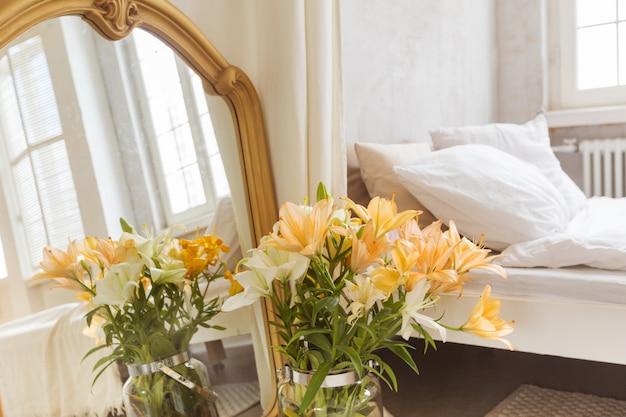 Buquê de flores de lírios e espelho colocado perto da cortina e cama confortável no quarto elegante em casa