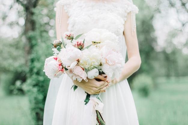 Buquê de flores de peônia rosa e branca de beleza nas mãos da noiva.