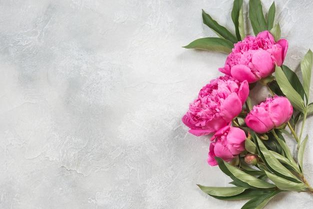 Buquê de flores de peônia rosa na mesa vintage. copie o espaço.