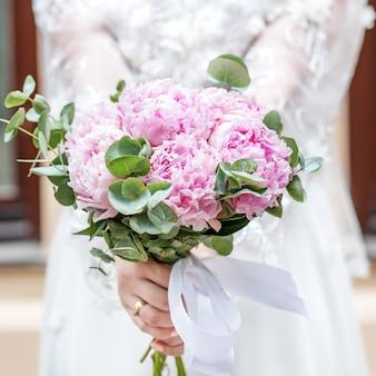 Buquê de flores de peônia rosa nas mãos da noiva