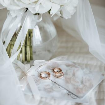 Buquê de flores de peônias em um vaso fica na cama dos noivos com convites e anéis no fundo de um véu da noiva