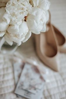 Buquê de flores de peônias em um vaso fica na cama dos noivos com convites e sapatos no espaço dos vestidos de noiva