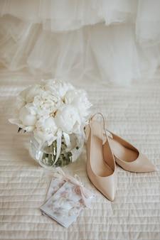 Buquê de flores de peônias em um vaso fica na cama dos noivos com convites e sapatos no fundo dos vestidos de noiva