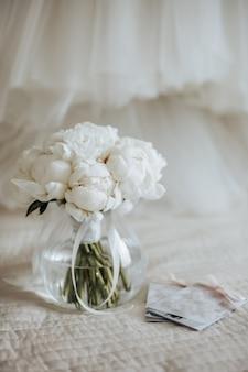 Buquê de flores de peônias em um vaso fica na cama dos noivos com convites