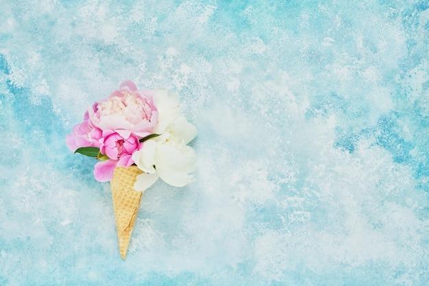 Buquê de flores de peônias na casquinha de sorvete waffle, plano de fundo do feriado. conceito de verão. copie o espaço