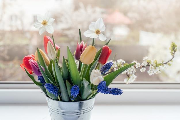 Buquê de flores de primavera no parapeito da janela, dia da mulher e cartão de felicitações de páscoa