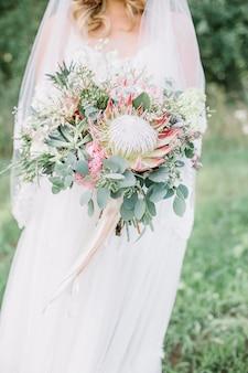Buquê de flores de protea, suculentas e ramos de eucalipto nas mãos da noiva.