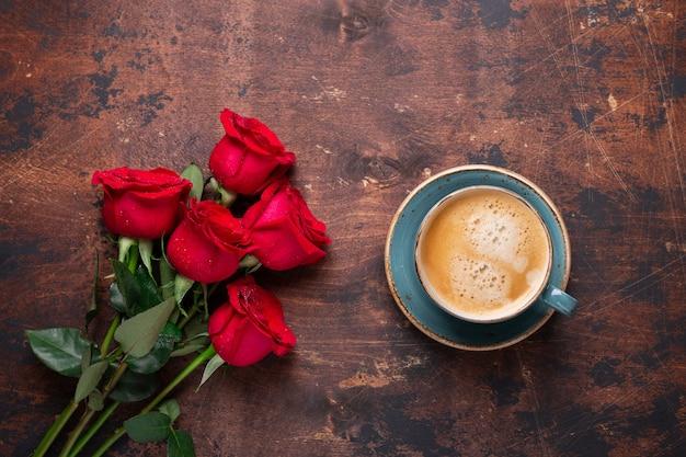 Buquê de flores de rosas vermelhas e xícara de café sobre fundo de madeira