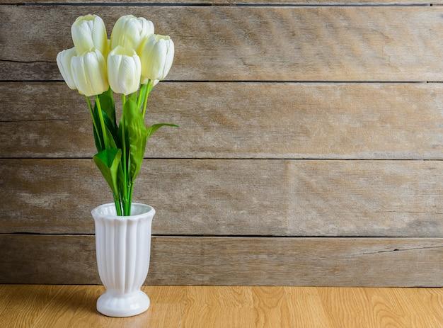Buquê de flores de tulipa branca em um vaso no chão de madeira