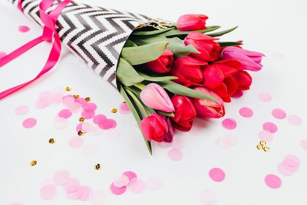 Buquê de flores de tulipa da primavera e confetes. disposição plana, vista de cima