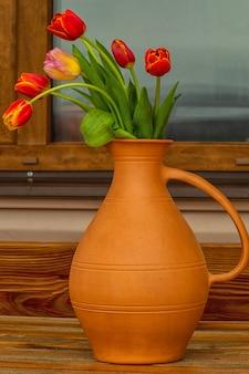 Buquê de flores de tulipa em um vaso de barro, ao ar livre.