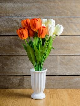Buquê de flores de tulipa laranja, branco em um vaso no chão de madeira