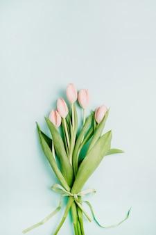 Buquê de flores de tulipa rosa sobre fundo azul. camada plana, vista superior