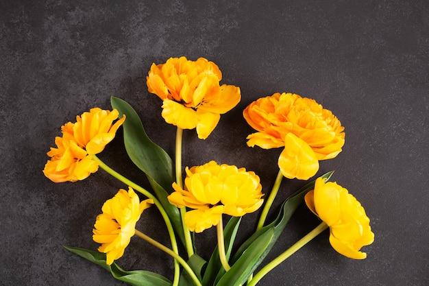 Buquê de flores de tulipas amarelas em superfície escura