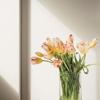 Buquê de flores de tulipas amarelas em um vaso de vidro contra a parede branca