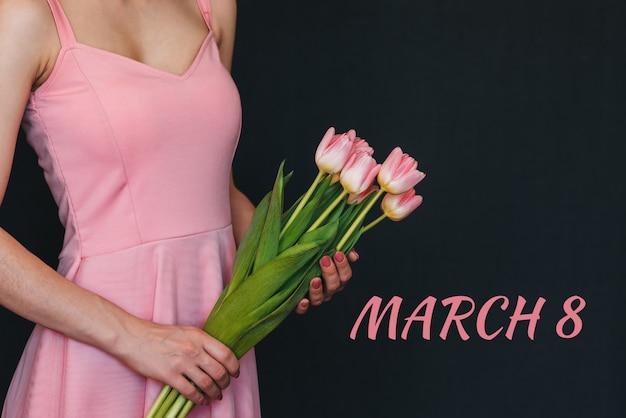 Buquê de flores de tulipas cor de rosa nas mãos de uma menina. cartão com texto 8 de março