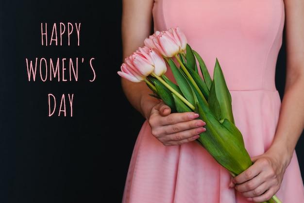Buquê de flores de tulipas cor de rosa nas mãos de uma menina