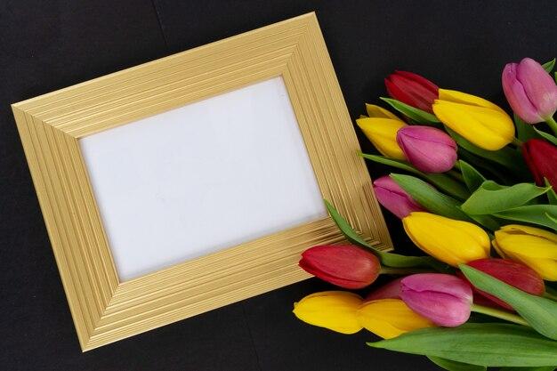 Buquê de flores de tulipas rosa, vermelhas e violetas com corações sobre fundo preto com cópia spae na moldura dourada