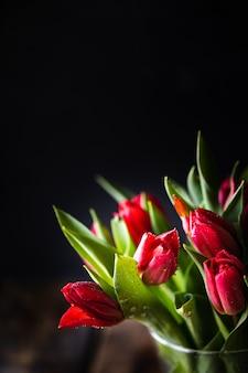Buquê de flores de tulipas vermelhas closeup e folhas verdes em preto