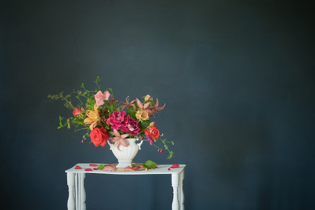 Buquê de flores de verão em um vaso na prateleira de madeira branca vintage em fundo escuro