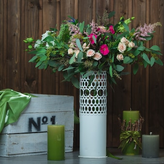 Buquê de flores dentro de vaso decorativo branco.