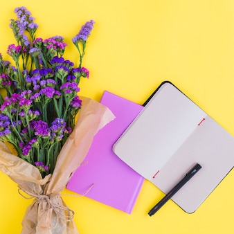 Buquê de flores; diários e caneta no pano de fundo amarelo