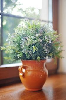 Buquê de flores do campo em uma panela no peitoril da janela