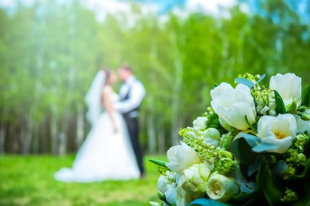 Buquê de flores do casamento com casal recém-casado